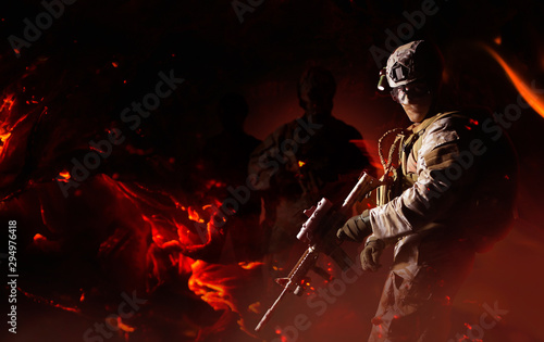 Fotomural  Fully equipped desert soldier standing with rifle on fire background