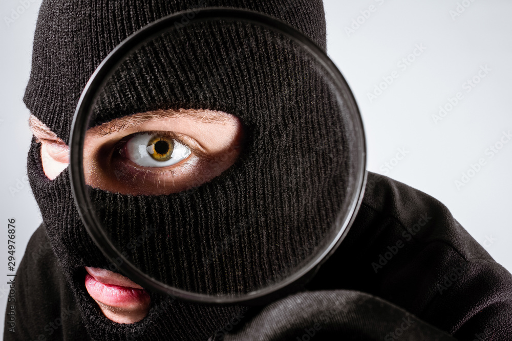 Fototapeta Male thief looking at magnifying glass.