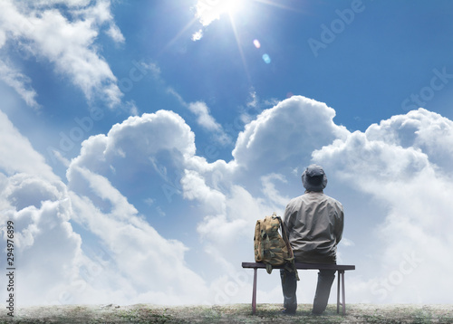 Male traveller sitting on a bench on a sunny day. Wallpaper Mural