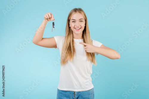 Fototapeta happy smiling blonde woman with keys from apartment isolated over blue obraz na płótnie