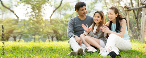 Fototapeta  Asian family is Sitting and chatting the park, which is ideal picnic for long weekend vacations