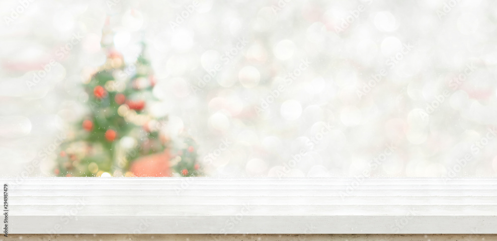 Fototapeta Empty white wood table top with abstract warm living room decor with christmas tree string light blur background with snow,Holiday backdrop,Mock up banner for display of advertise product
