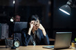 Asian business woman working late sitting on desk in office at night. The girl feeling stress and tired after overload job has been assigned. Lady hold glasses up and hand on nose. Boss sits behind.