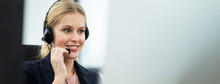 Beautiful Caucasian Female Call Center With Headset Talking To Customer In Office. The Girl Working As Technical Service Support. Seen Behind The Back Of Computer Monitor In Banner Size.
