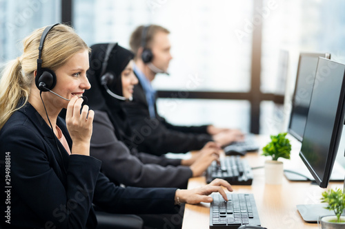 Fototapety, obrazy: Beautiful Caucasian female call center with headset talking to customer in office. The girl holding headphone microphone with smile. Seen from woman side with colleagues muslim girl and Caucasian man.