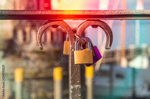 Fotografía  Love padlocks on a railing in the harbor on blurred lighthouse b