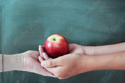 Photo sur Toile Pays d Asie Student and teacher hands holding red apple with chalkboard background, Happy teacher's day, health, give and donate concept