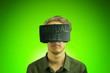 canvas print picture - Young man in a shirt uses virtual reality glasses with the inscription virtual life on them in front of a ufo green background