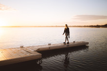 Girl Walking Along The South Perth Foreshore At Sunrise, Taking In The Views Of The City As The Sun Rises Over The Swan River.