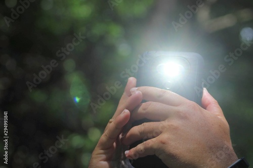 Obraz Hands hold cell phone with flash on - fototapety do salonu