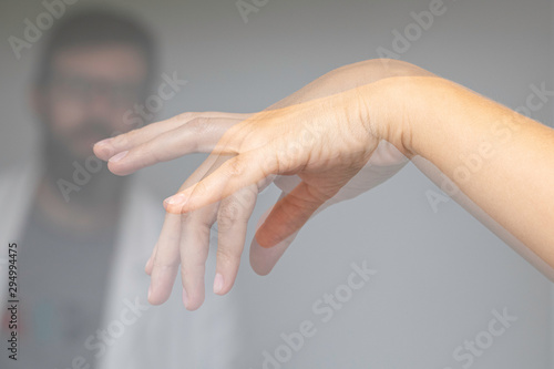 Photo Doctor wathing shaking hand of a person suffering from Parkinson's disease
