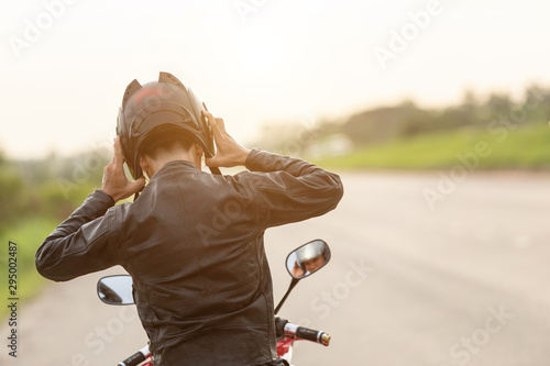 Valokuvatapetti Handsome motorcyclist wear leather jacket and holding helmet on the road