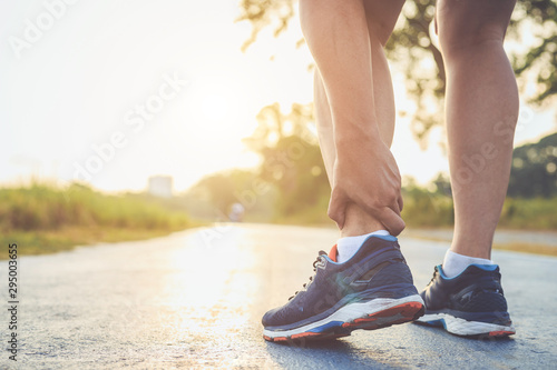 Photo Injury from workout concept : Asian man use hands hold on his ankle while running on road in the park