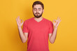 Close up portrait of attractive man dresses red casual t shirt gesturing ok sign with closed eyes and both hands , model posing isolated over yellow background in studio. Meditation concept.
