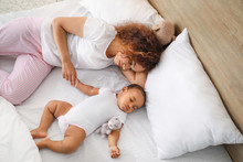 Young African-American Woman And Her Baby Sleeping On Bed