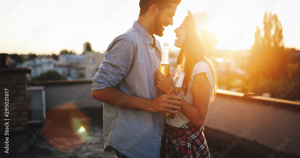 Fototapety, obrazy: Happy young couple enjoying drinks and balcony