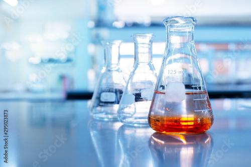 Obraz orange solution in science glass flask in blue chemistry school laboratory background - fototapety do salonu