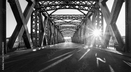 fototapeta na szkło Black and white asphalt road under the steel construction of a bridge in the city on a sunny day. Evening urban scene with the sunbeam in the tunnel. City life, transport and traffic concept.