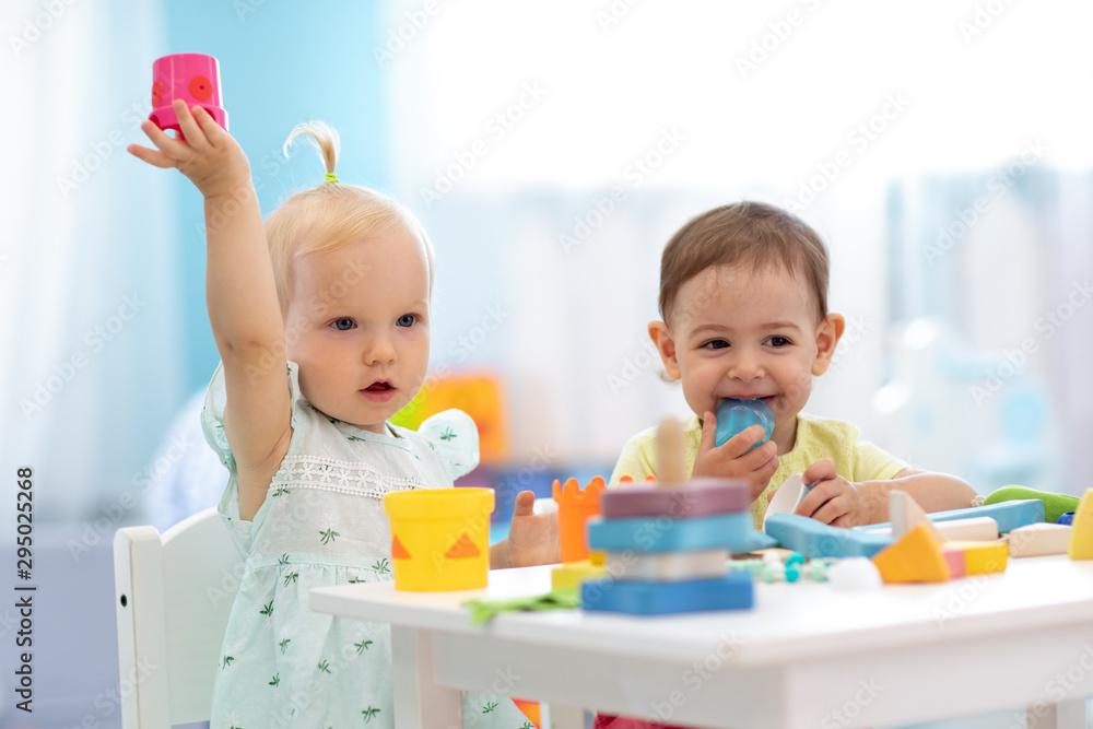 Fototapety, obrazy: Little kids playing in creche or nursery. Developmental toys for preschool.