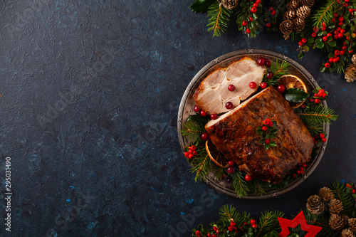 Roast pork neck in Christmas style. Dark navy blue background. Christmas accessories. Top view. - 295031490