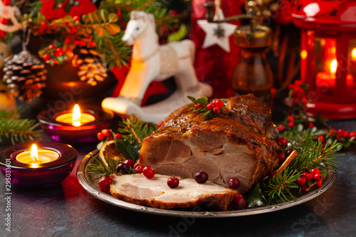 Roast pork neck in Christmas style. Dark navy blue background. Christmas accessories. Candles and lanterns in the background. - 295031601