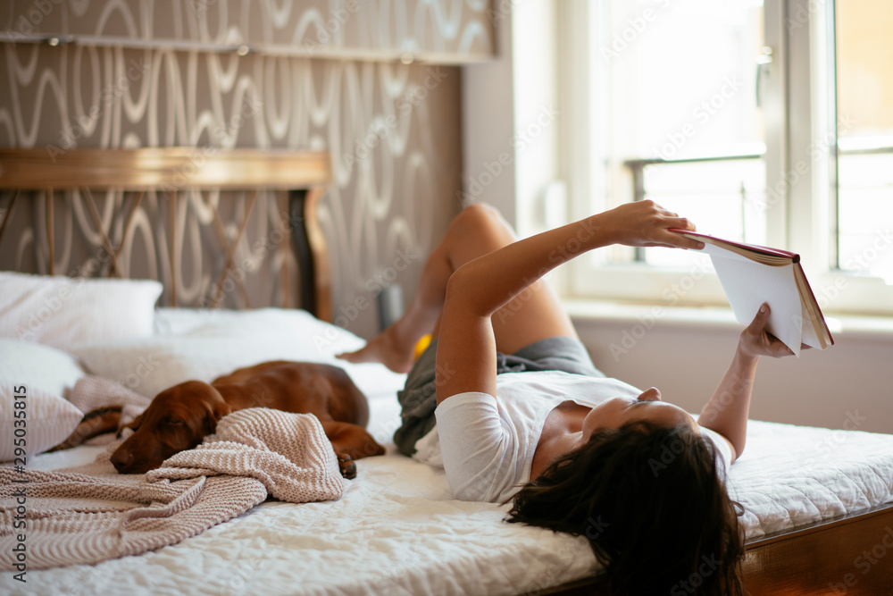 Fototapeta Young woman with dog  lying on bed while reading book