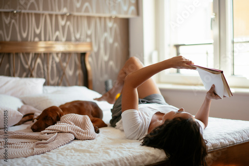 Obraz Young woman with dog  lying on bed while reading book - fototapety do salonu
