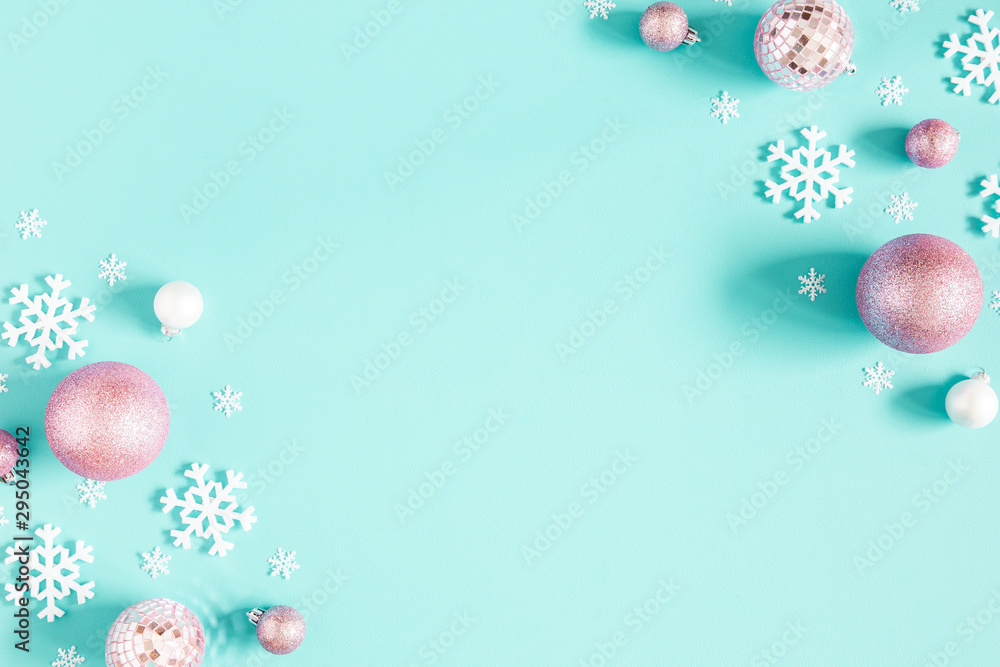 Fototapeta Christmas composition. Frame made of pink balls and white snowflakes on pastel blue background. Christmas, winter, new year concept. Flat lay, top view, copy space