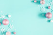Leinwandbild Motiv Christmas composition. Frame made of pink balls and white snowflakes on pastel blue background. Christmas, winter, new year concept. Flat lay, top view, copy space