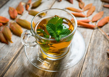 Hot Mint Tea In Glass Cup With Atmospheric Autumn Decorations. Selective Focus. Shallow Depth Of Field.