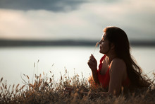 Foreground Of A Beautiful Girl In A Red Dress Holding A Blade Of Grass Luying Down On The Coast Near The Water
