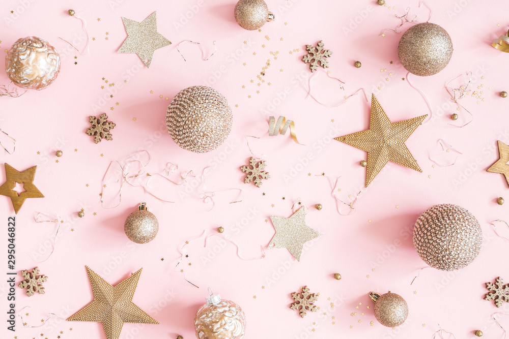 Fototapeta Christmas composition. Golden decorations on pastel pink background. Christmas, winter, new year concept. Flat lay, top view