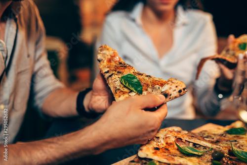 Photo  closeup friends eating pizza. night scene