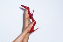 Isolated Female Legs In Red High Heels. Studio Shoot.