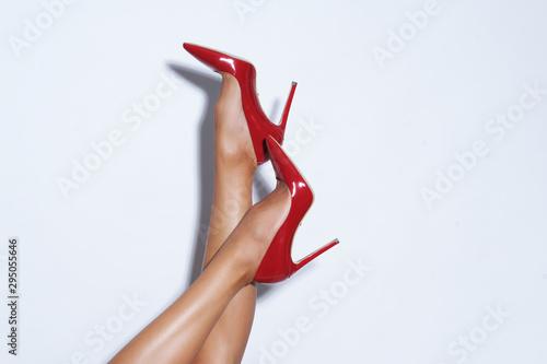 Fotografia, Obraz Isolated female legs in red high heels. Studio shoot.