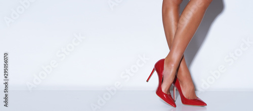 Fotografia Cropp picture of female legs standing on white background.