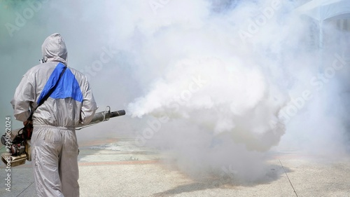 Obraz Rear view of  outdoor healthcare worker using fogging machine spraying chemical to eliminate mosquitoes and prevent dengue fever at general location in community - fototapety do salonu