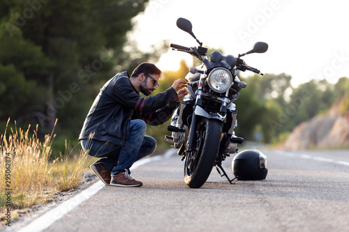 obraz lub plakat Young man biker checking his motorbike before driving it on the road.
