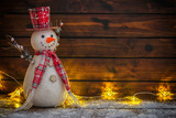 Fototapeta Tulipany - Christmas background with Christmas lights and snowman on the old wooden board