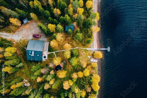 Slika na platnu Aerial view of cottage in autumn colors forest by blue lake in rural Finland