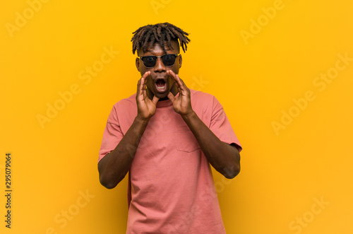 Young casual black man wearing sunglasses shouting excited to front Canvas Print