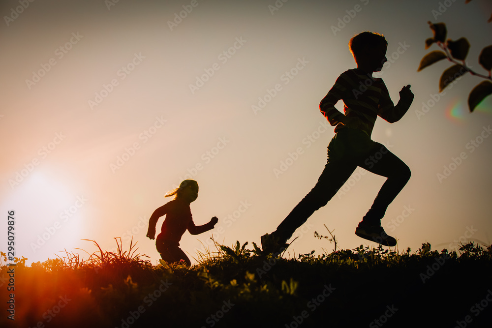 Fototapety, obrazy: Silhouette of happy boy and girl running at sunset