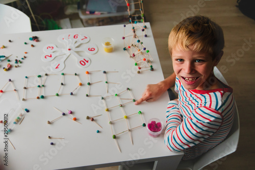 boy making letters, geometric shapes from sticks and clay, engineering and STEM