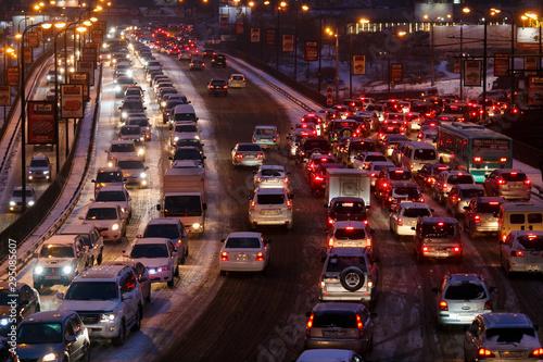Fototapeta Car traffic jams due to snowfall in the evening.