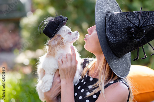 Fototapeta  Cheerful tender young blond woman holding a charming fluffy dog in her arms dressed in witcher Halloween costumes and black hats on a warm autumn day