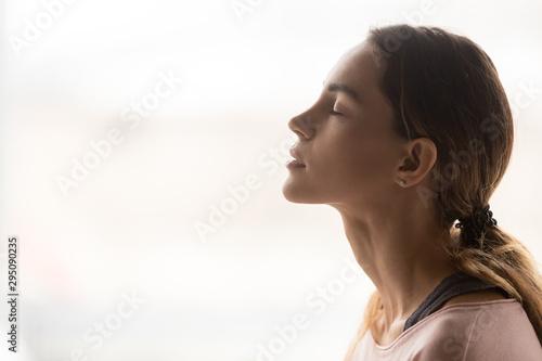 Serene young woman taking deep breath of fresh air