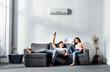 canvas print picture - handsome boyfriend switching on air conditioner and looking at smiling girlfriend