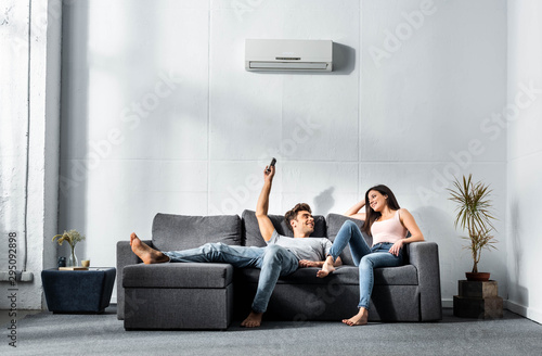 Photo handsome boyfriend switching on air conditioner and looking at smiling girlfrien