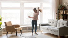 Happy Carefree Young Woman Dancing Alone Having Fun At Home