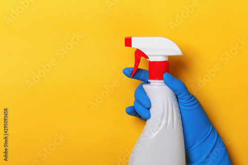A hand in a latex protective glove holds a spray bottle on a yellow background Wallpaper Mural